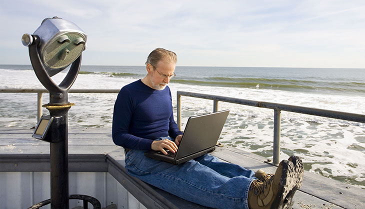 Man sitting at the sea with laptop